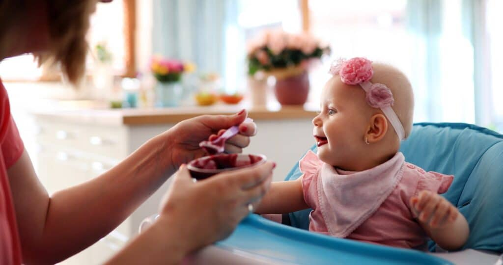 Pleasant young woman feeding a cute baby
